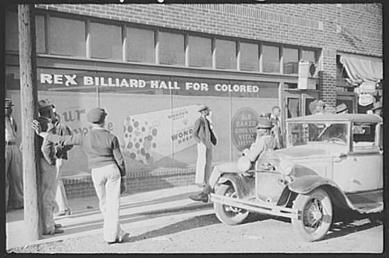 A group of black men and an old car standing outside a billiard hall.