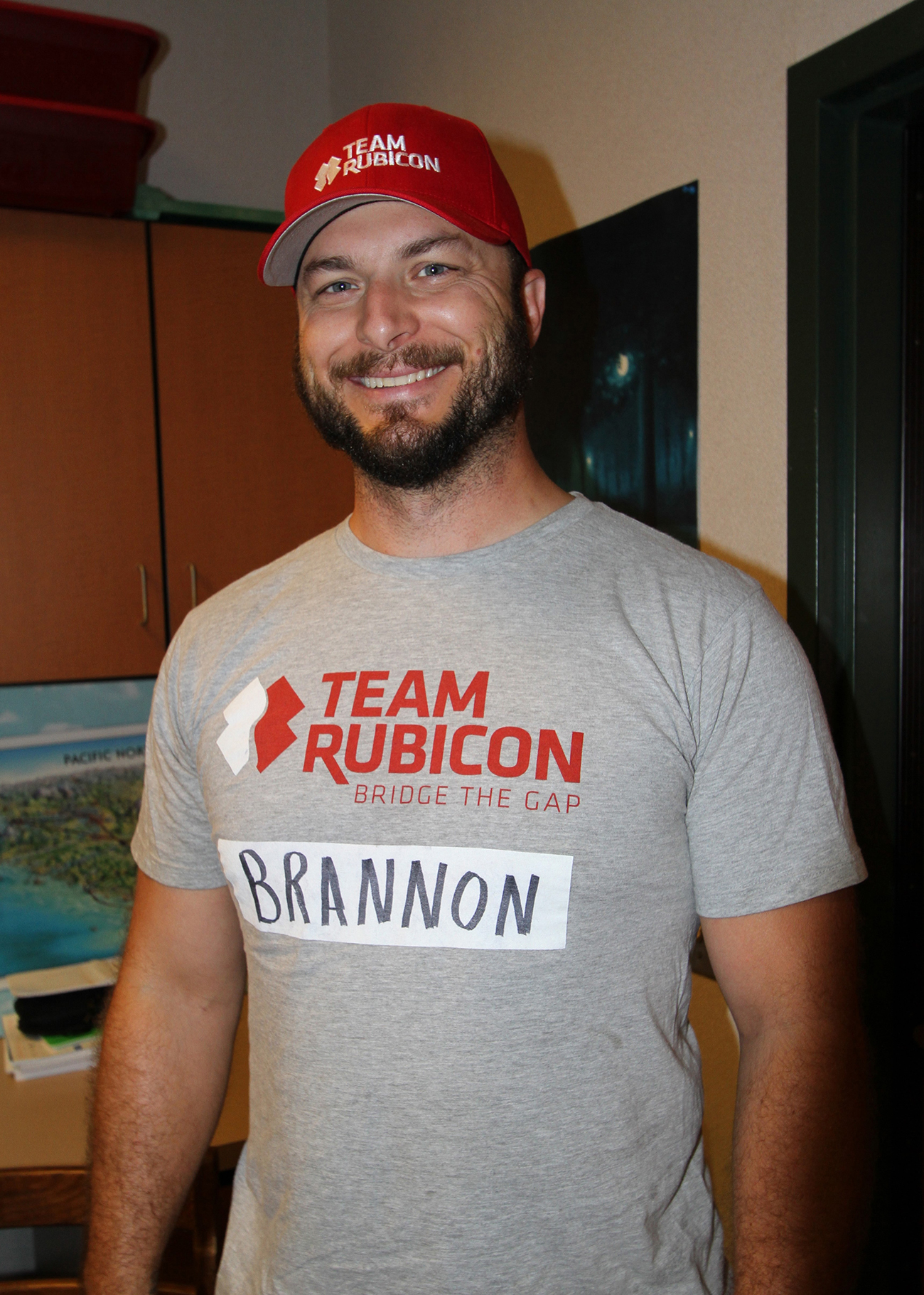 Photograph shows a man wearing a Team Rubicon hat, and Team Rubicon shirt.
