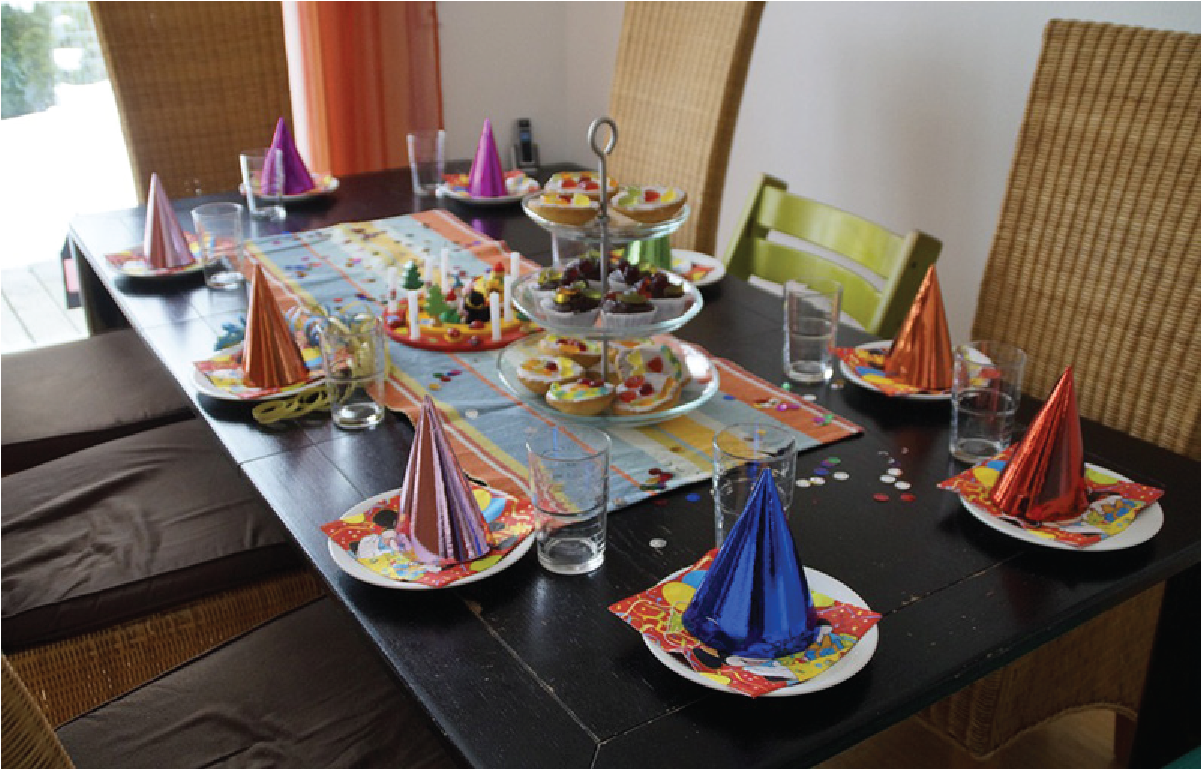 Photo of a table set for a party, with fancy party hats, napkins, and platters of cookies.