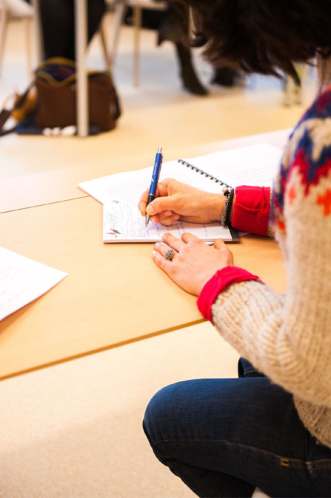 A student takes down notes on a notebook inside a classroom.