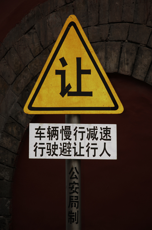 The photo (b) shows a sign with writing in Chinese.