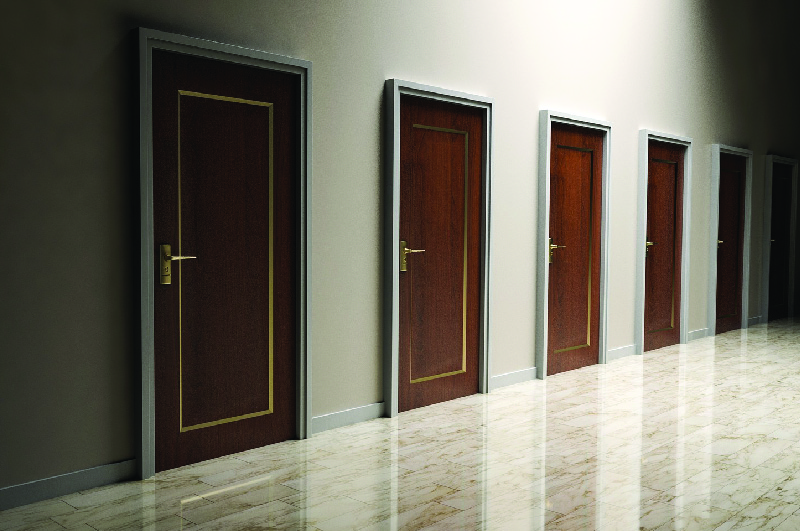 This image shows a row of six doors along the wall of an empty room.