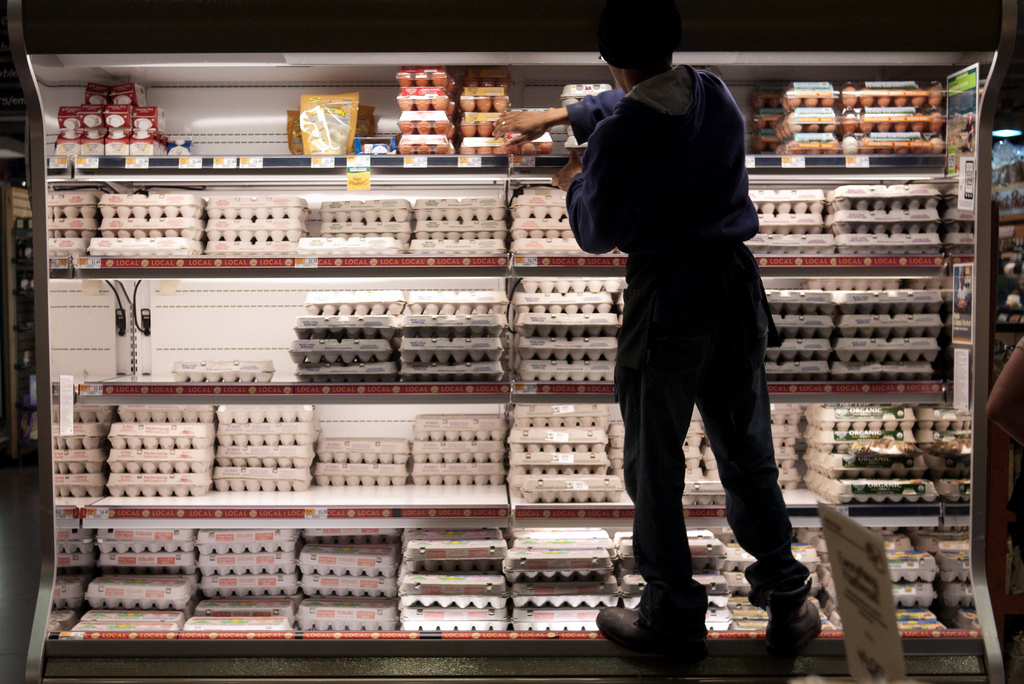 A staff stacks eggs on the shelves at a supermarket.