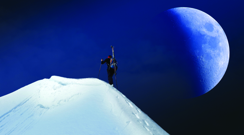 This image shows a person hiking up a snow-covered mountain. The moon is half-full and off to the right of the mountain and the hiker. It appears very large in the sky and very close to the hiker.