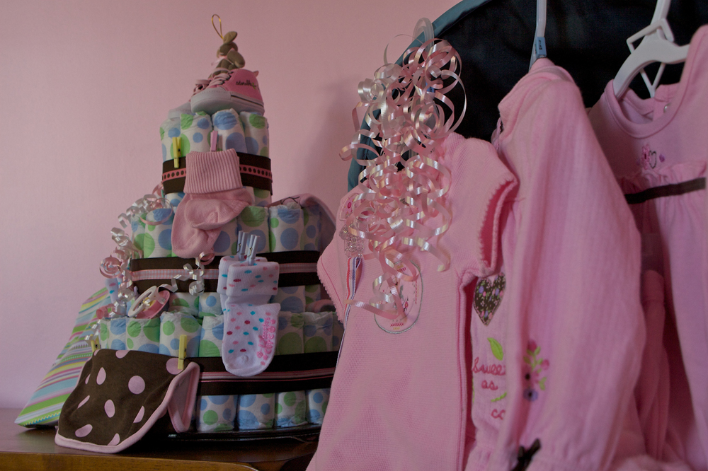 Pink baby clothes and other baby shower gifts are shown here.