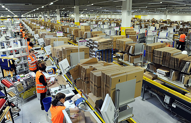 A photo shows a view of an Amazon logistics center with employees packing parcels to be shipped.