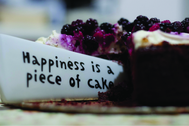 This image shows a knife cutting into a piece of cake. The knife says happiness is a piece of cake.