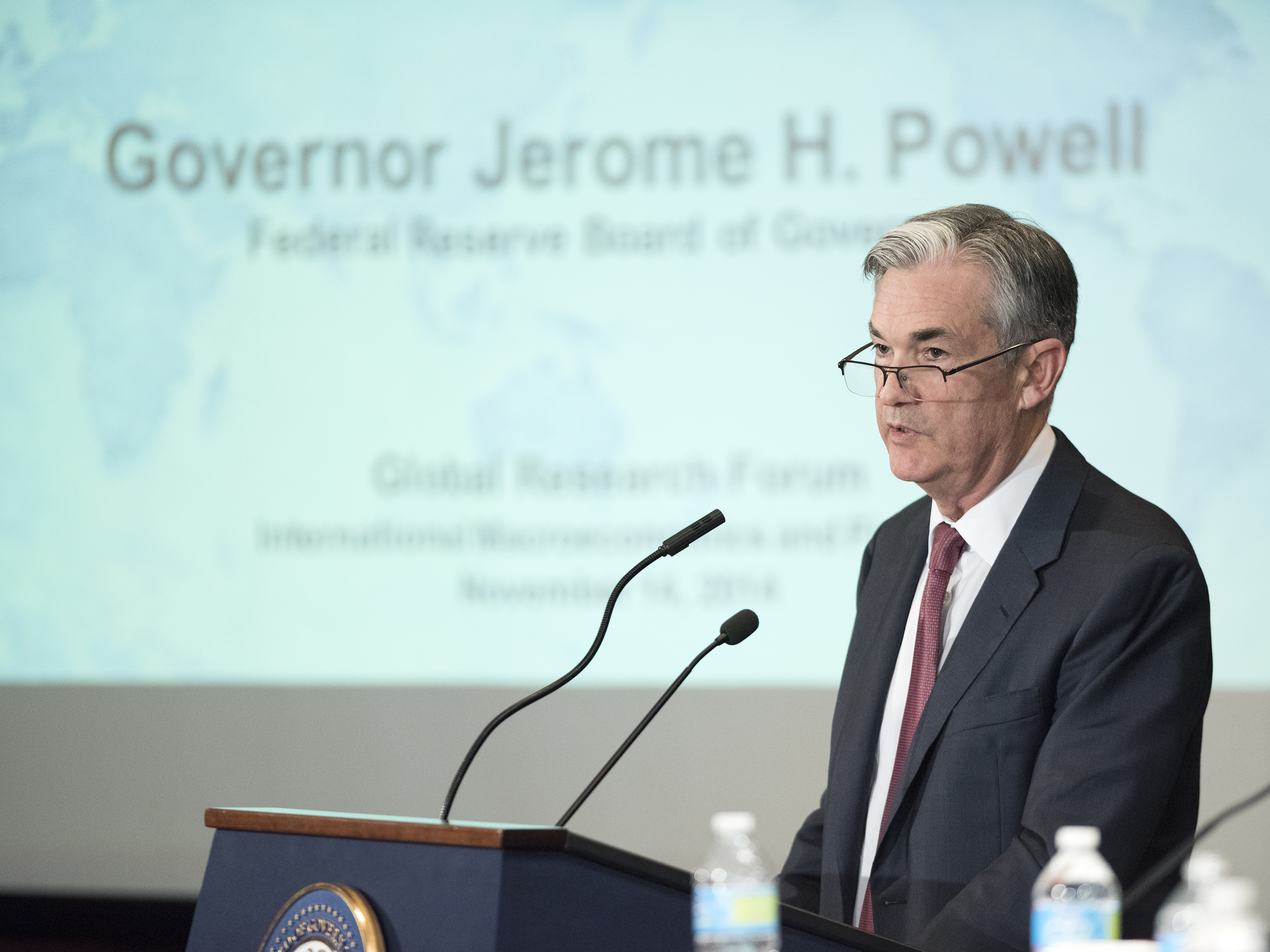 A photograph shows Fed Chairperson Jay Powell speaking at a podium.