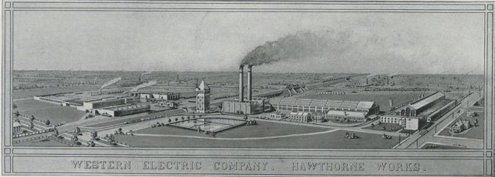 An image of a factory complex with two functioning smokestacks and a number of buildings is shown.