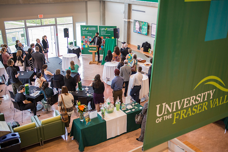A photo shows students attending an alumni event at the University of the Fraser Valley, as a member of the alumni association delivers a speech.