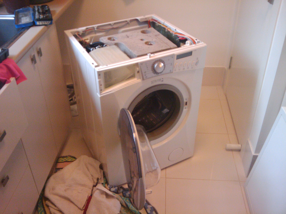 A broken washing machine is shown with not top cover.