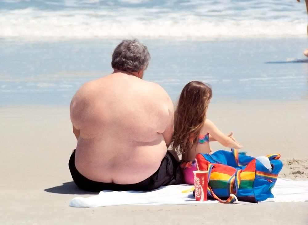 A large man is shown here sitting on a beach with a young girl.