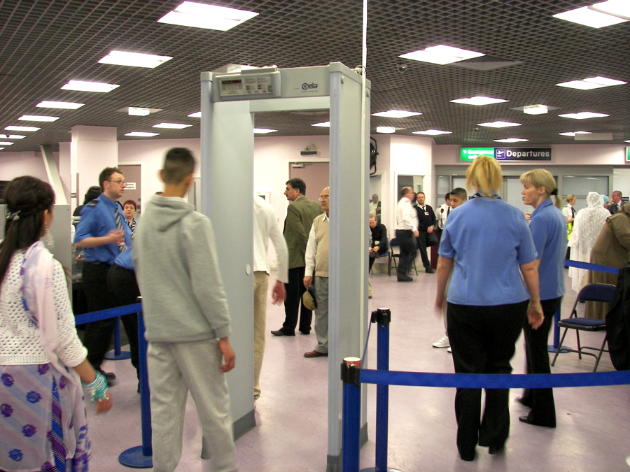 Photograph of people around a security gate at an airport departure terminal.
