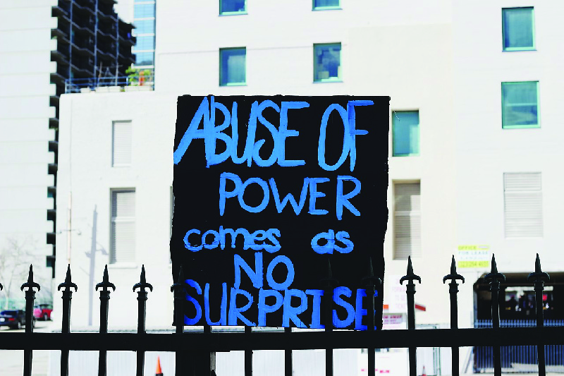 "This image shows a hand-painted sign that says ""Abuse of power comes as no surprise."""