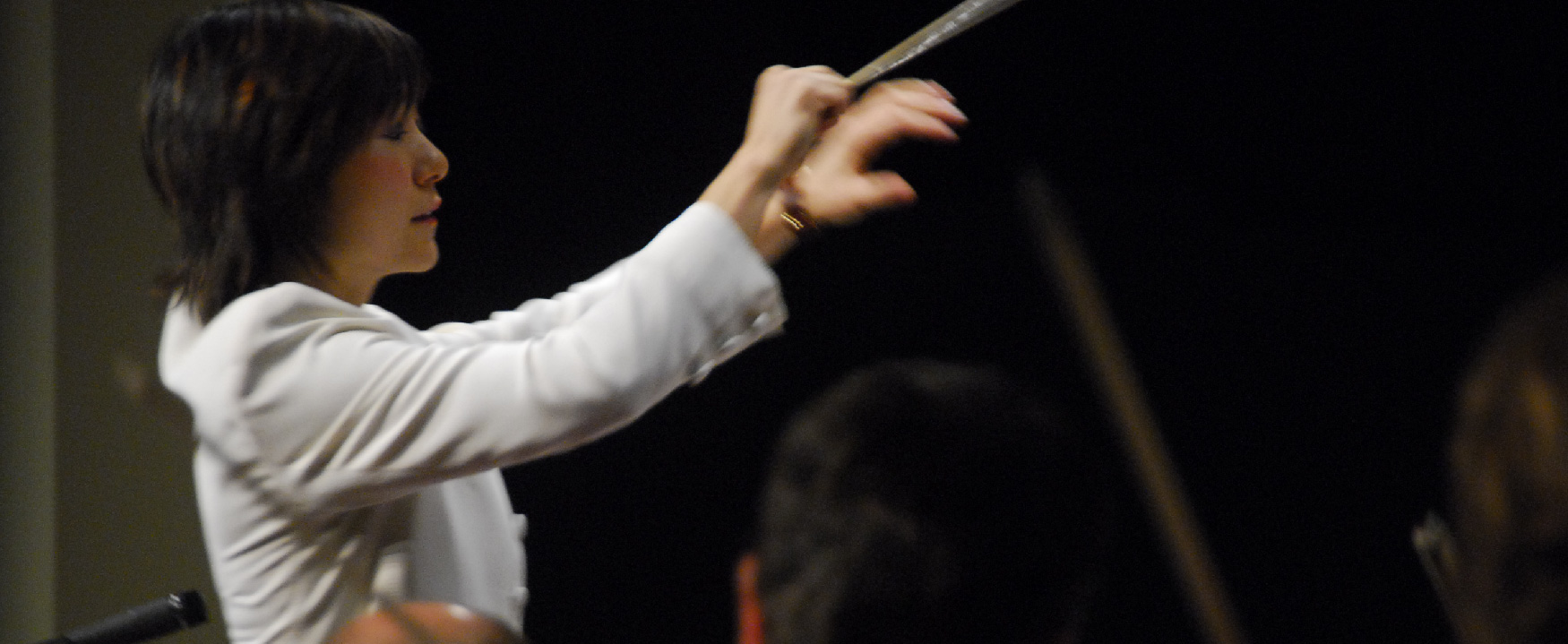 A photo shows the side view of a female orchestra conductor directing her orchestra.