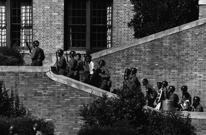 An image of armed people in helmets, escorting several children up a brick stairway.