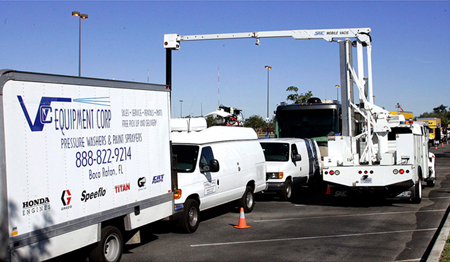 The picture shows a series of trucks headed in one direction. A truck pointed in the opposite direction has a crane with a device over the middle truck.