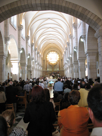 Numerous people are shown from behind standing in a church.