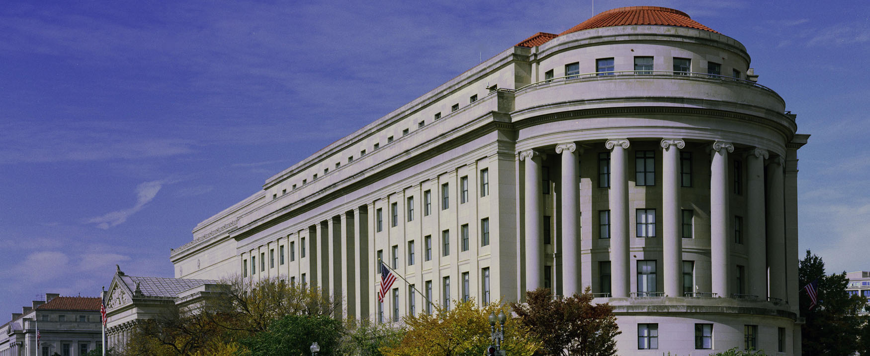 A picture of the United States Federal Trade Commission building in Washington DC.  The seven-story building is made of gray-white granite.  One end of the building is rounded with large pillars.  The rest of the building is rectangular.