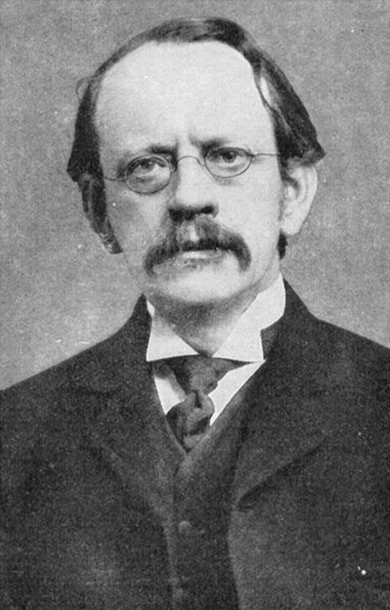 A black and white image of scientist J. J. Thomson wearing a coat and oval shaped spectacles.