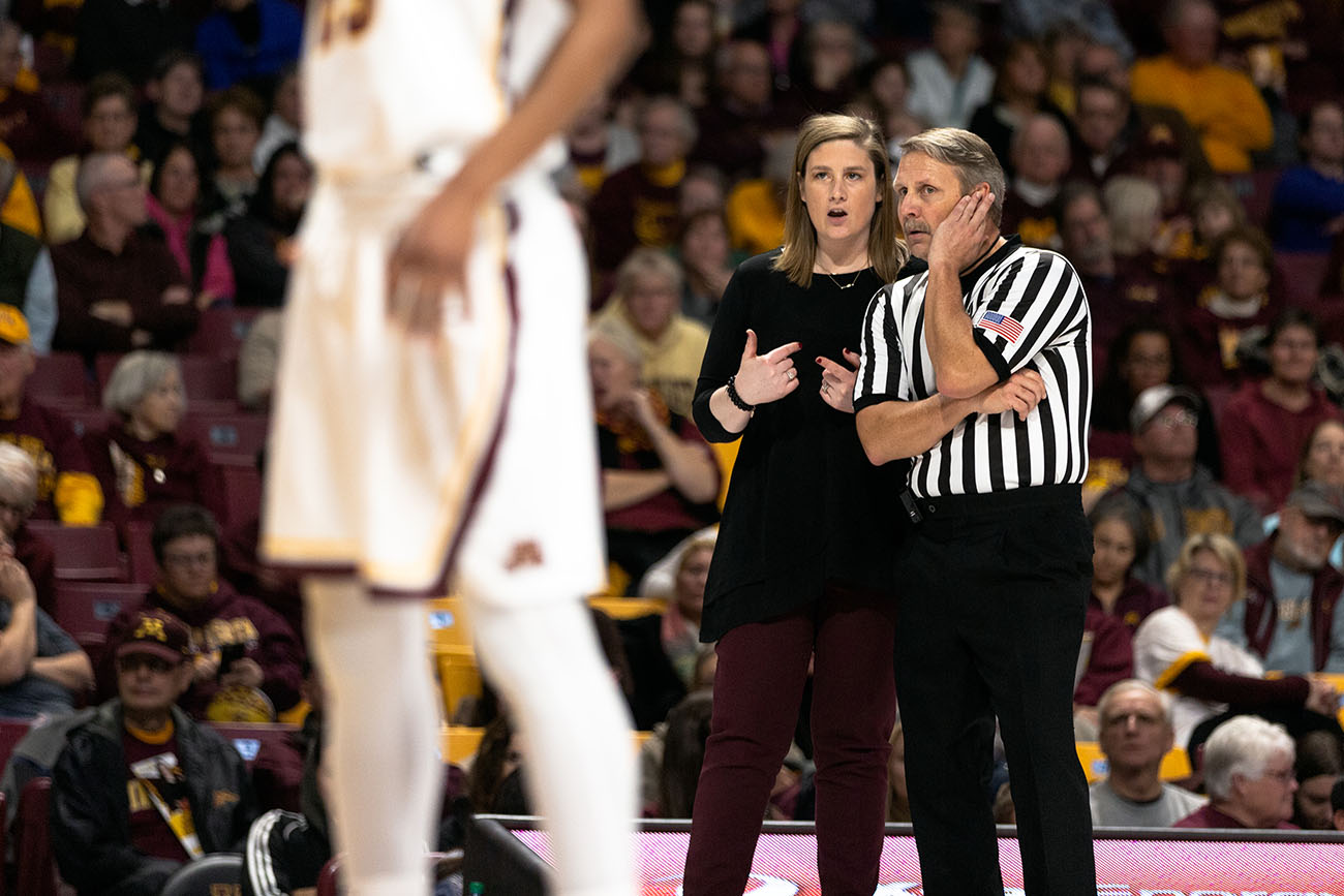 A photo shows Minnesota Gophers coach, Lindsay Whalen talking to a referee during a University of Minnesota Gophers game against Cornell University.