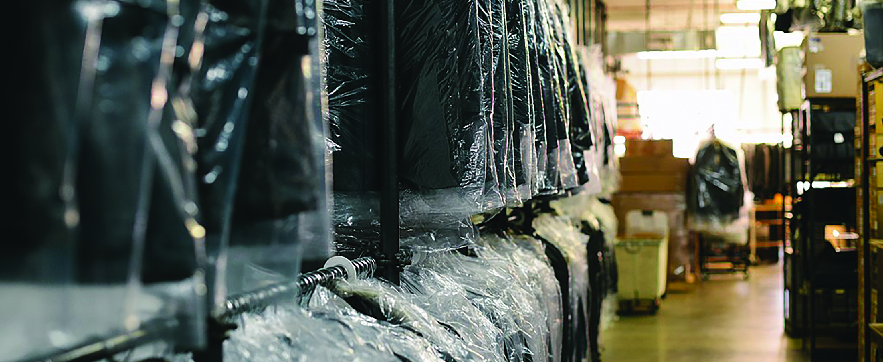 View of interior of dry-cleaning business. On the left are racks of clothes covered in plastic. On the right are shelves holding boxes.