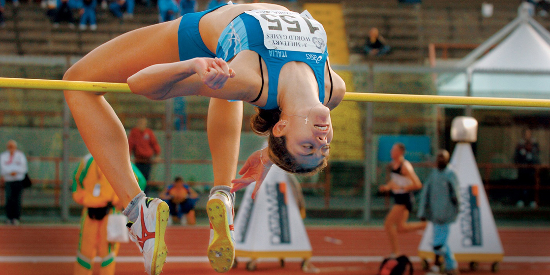 Photo shows a woman, upside-down with an arched back, going over a horizontal bar at a track and field event.