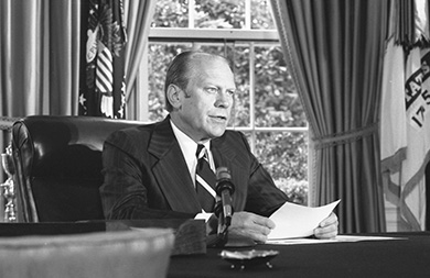 A photograph shows Gerald Ford seated at a desk with a sheet of paper before him, speaking into a microphone.