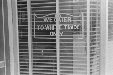 "A photograph shows a shop window bearing a sign that reads ""We cater to white trade only."""