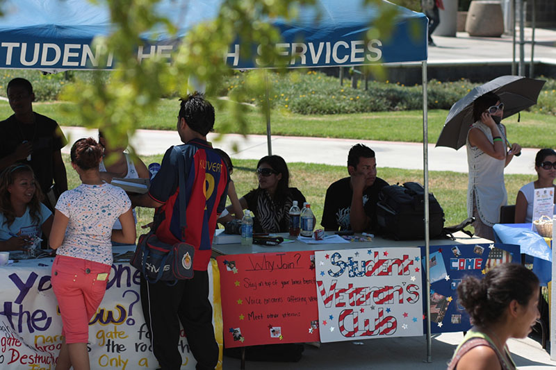A photo shows people sitting at tables during a college club showcase fair, while prospective members speak to them and look at materials. The tables are decorated with signs for clubs including the Student Veteran's Club.