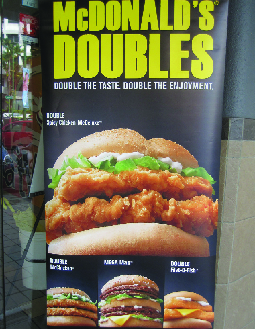 "This image shows an advertisement for McDonald's Doubles. It says ""Double the taste. Double the enjoyment."" It shows four sandwiches: the Double Spicy Chicken McDeluxe, the Double McChicken, the Mega Mac, and the Double Filet-O-Fish."