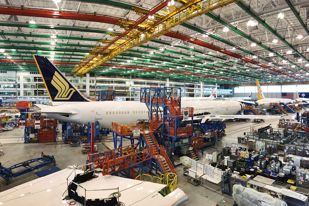 A photograph shows a large indoor area filled with airplanes, and machines and computers.
