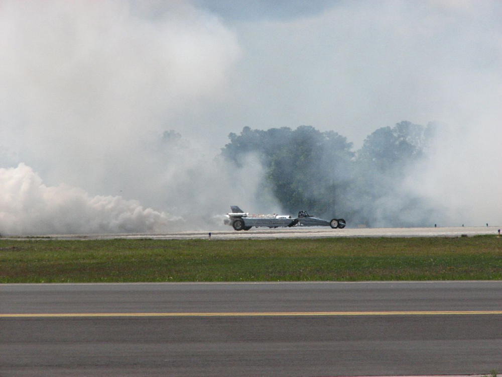 A photo shows a U S Air Force jet speeding down a track with a lot of smoke around it.