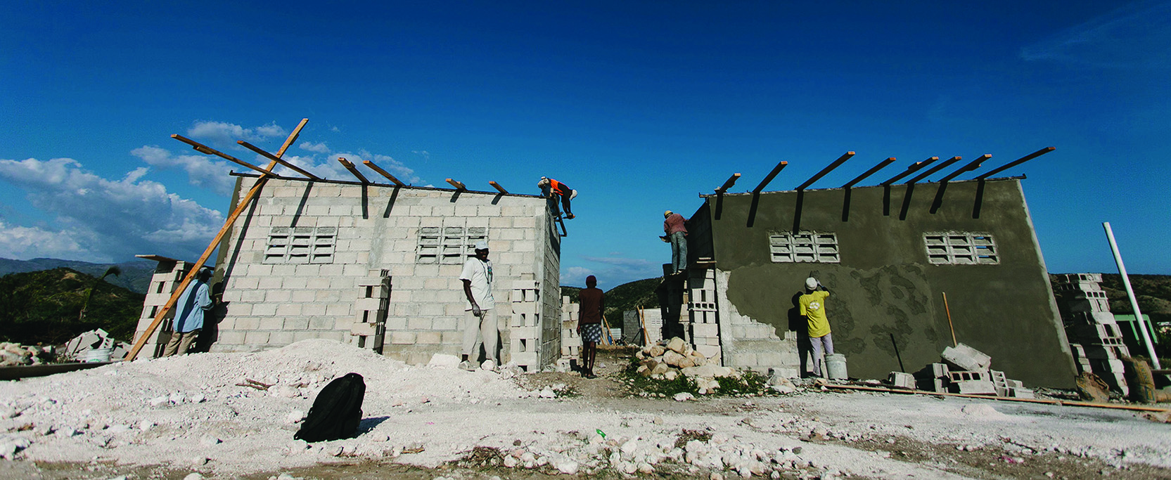 A photograph shows people building houses in Haiti.