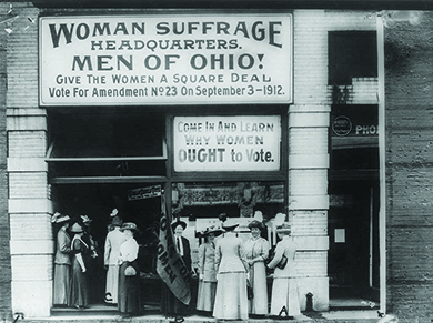 "A photograph shows women suffragists standing outside a building. The sign above them reads ""Woman Suffrage Headquarters. Men of Ohio! Give The Women A Square Deal. Vote For Amendment No. 23 on September 3—1912."" A second sign reads ""Come In And Learn Why Women OUGHT to Vote."""