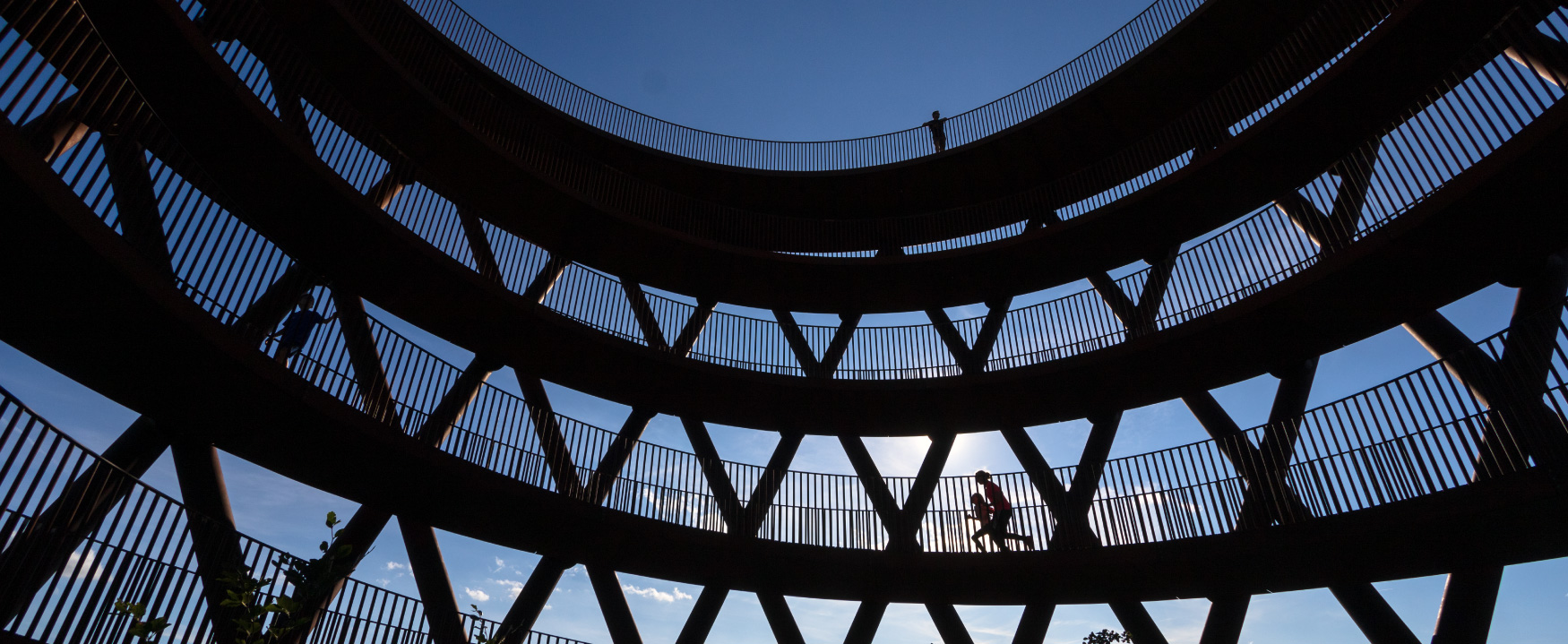A photo shows a low-angle view of silhouettes of people walking or running in the high observation tower, Camp Adventures in Haslev on the South Island of New Zealand.