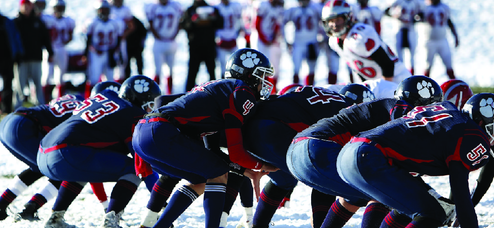 A photo of American football players lining up on the line of scrimmage.