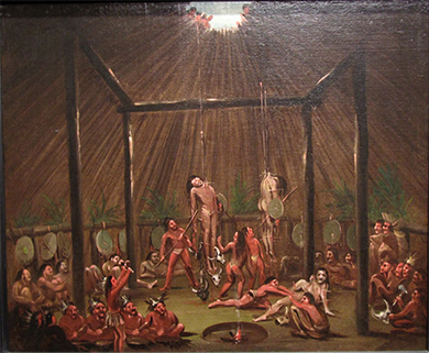 A painting shows several young Indian men suspended by wooden splints, which are stuck through different parts of their bodies. Others participate in the ritual or look on from below.