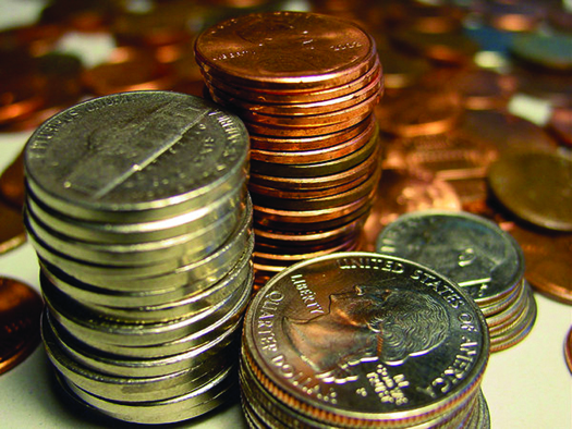 An image of a large stack of pennies, a large stack of nickels, a shorter stack of dimes, and a stack of quarters is shown. There are several coins in the background.