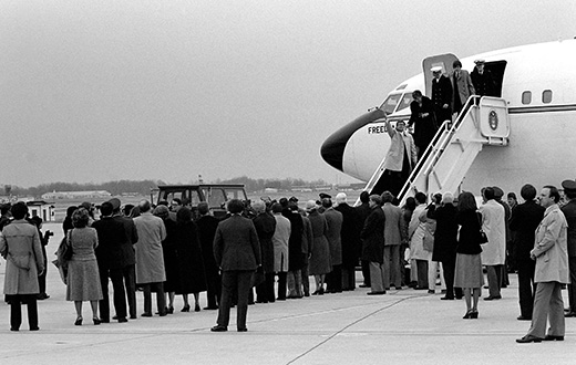 A photograph shows former hostages walking down a flight of steps to exit an official plane; a crowd of people waits for them on the ground.