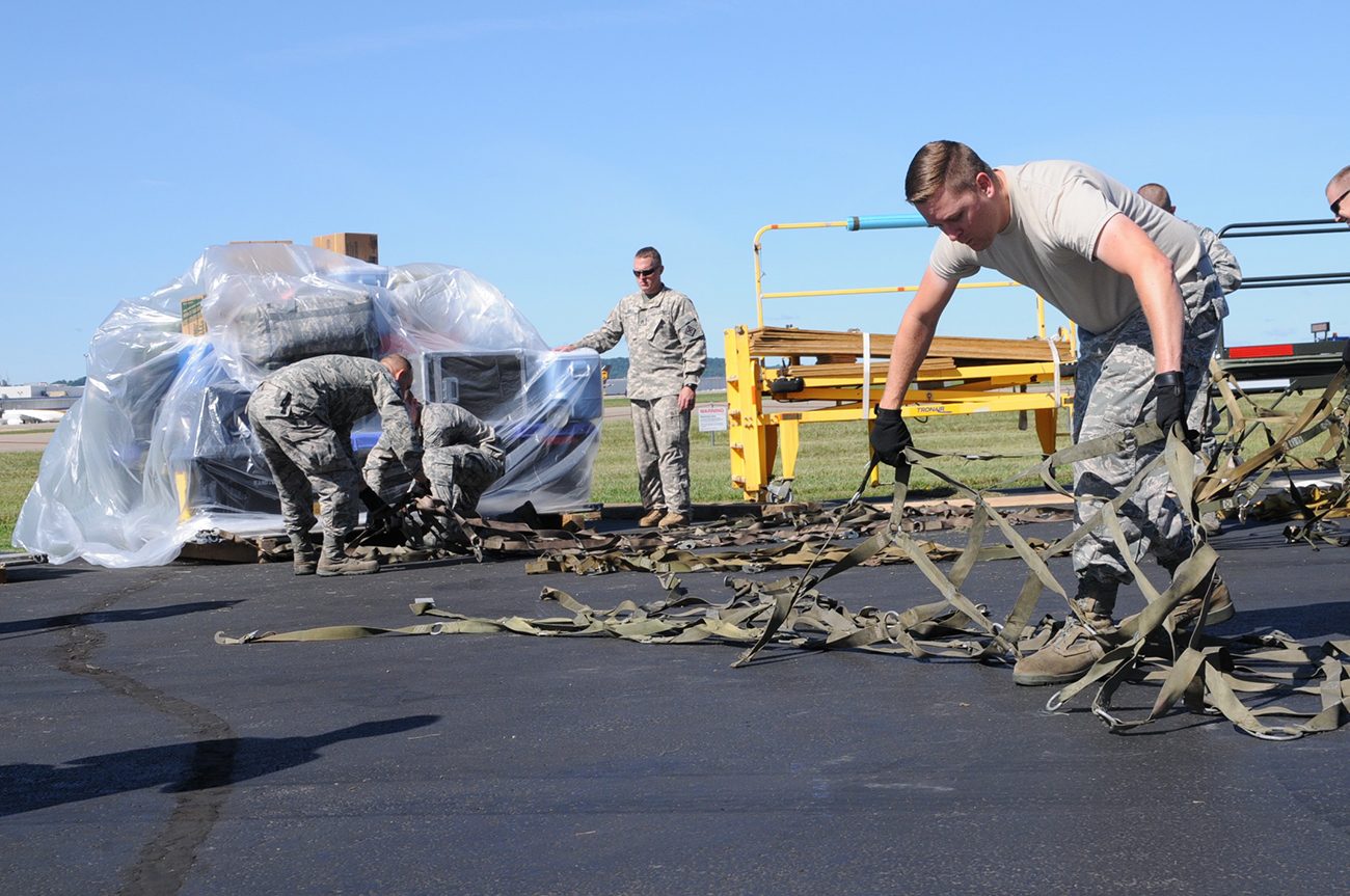 A photograph shows a group of men wearing military fatigues, using heavy duty strapping to secure a large pallet stacked with cargo.