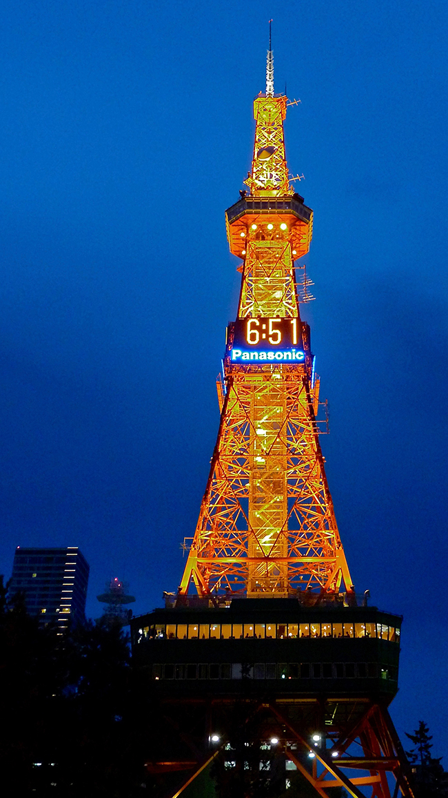 "A photo of the Sapporo TV tower with digital clocks installed on it at four sides. The digital clocks read ""6:51"" with the advertisement of Panasonic right below the clocks."