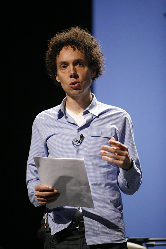 A photo of Malcolm Gladwell holding a paper and wearing a microphone.