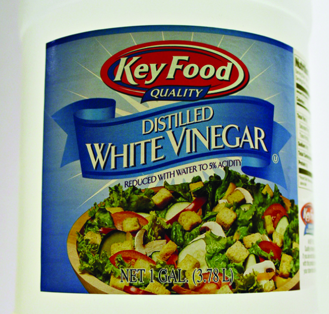 "A label on a container is shown. The label has a picture of a salad with the words ""Distilled White Vinegar,"" and, ""Reduced with water to 5% acidity,"" written above it."