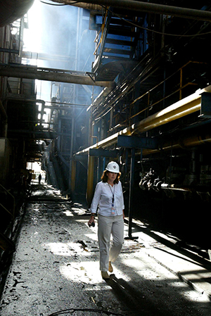 A woman wearing a hardhat walks between steaming pipes.
