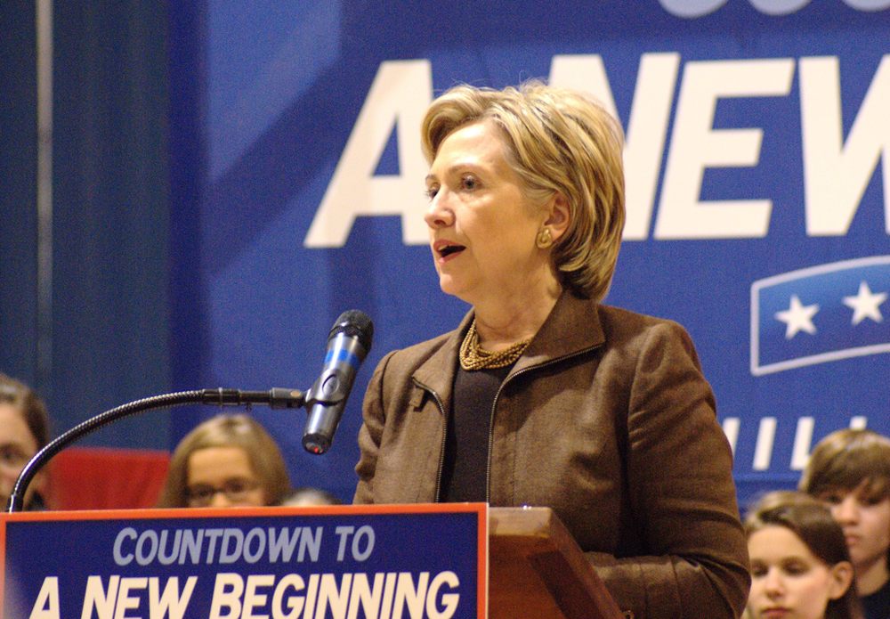 Then-presidential candidate Hillary Clinton is shown standing behind a podium with a placard stating: Countdown to a New Beginning. A number of children are shown in the background.