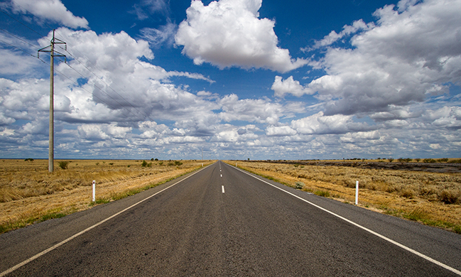 A photograph shows an empty road that continues toward the horizon.