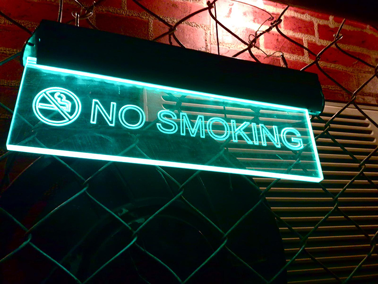 "A photo shows an illuminated ""No Smoking"" sign mounted on a fence."