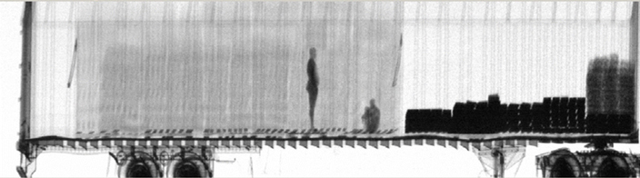 Gamma-ray scanned image of two stowaways hiding inside a big truck.