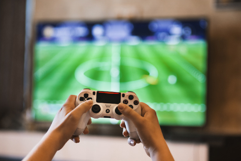 A photo shows hands operating a game controller and playing football on the Playstation.